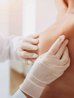 Doctor get examining breast of young woman. Consultation with gynecologist. Diagnostic, healthcare, medical service